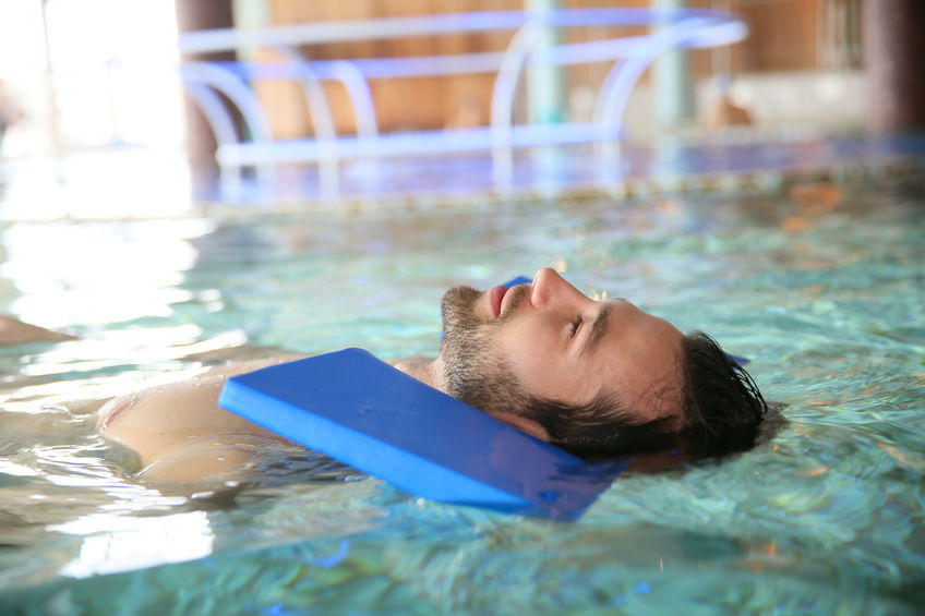 Man in pool doing exercises for muscular recovery