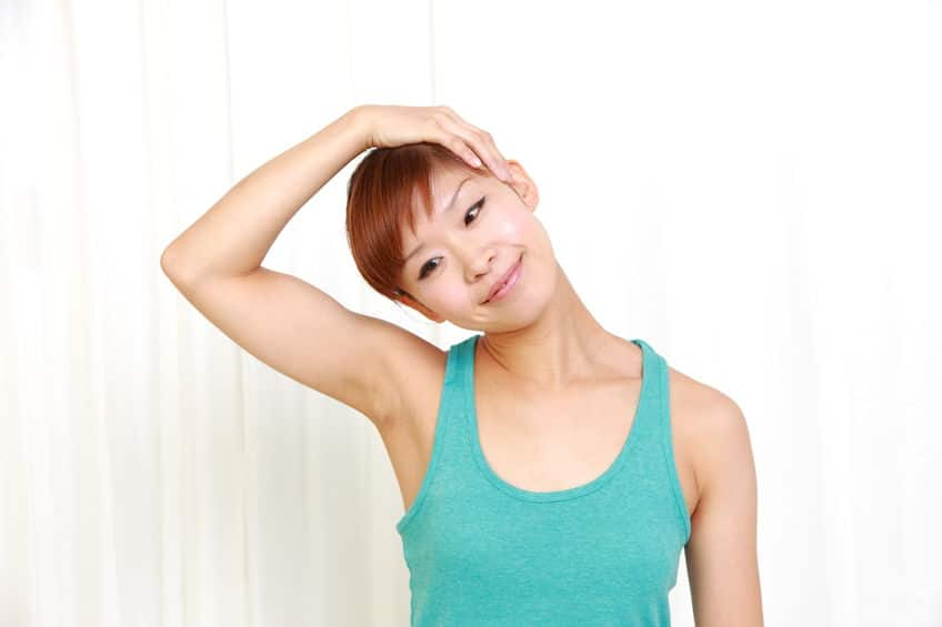 Young woman doing self neck stretch.